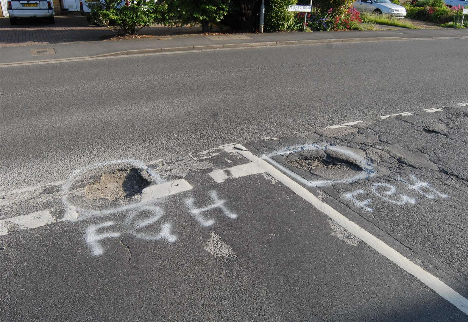 Updated: Graffiti artist praised for warning road users of dangerous potholes