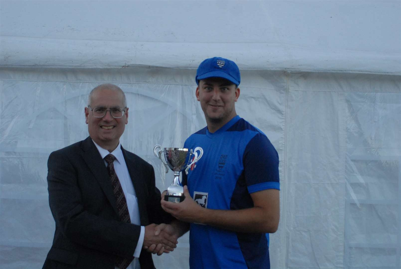 Bourne skipper Jack Berry receives the trophy from Eric Wagner, grandson of Dr Jaidka. (2771956)