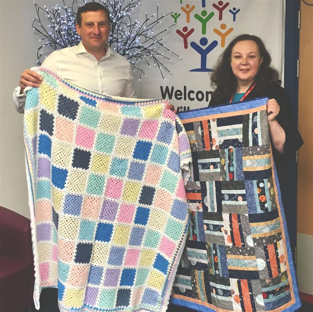 Buckles solicitor and Project Linus local co-ordinator, Alison Banerjee with James Husbands of Willoughby School, Bourne with some of the fantastic quilts