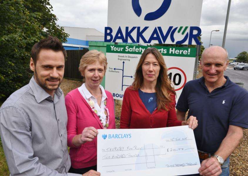 Ian Croom, Jenny Hollaway, and Annie Booth from Bakkavor in Bourne present a ?200 cheque to John Ogden from the Thurlby Fun Run committee. EMN-150622-234016009